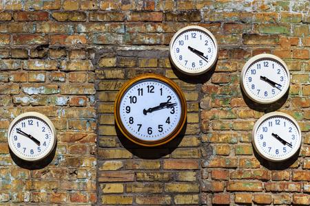 Oude klok op een bakstenen muur Stockfoto