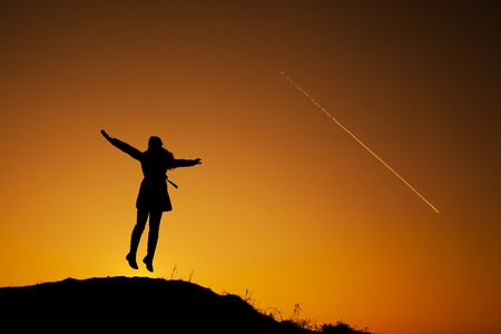 Young woman jumping on the top of the hill during winter sunset  Backlight landscape with airplane  Stock Photo - 12738598