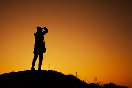 Young woman standing on the top of the hill during winter sunset  Backlight landscape