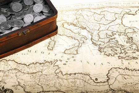 Old treasure chest full of polish zloty coins on map  Business and money concept