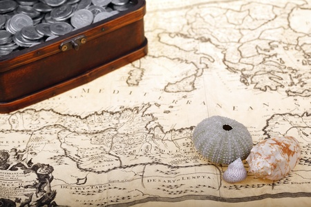land shell: Old treasure chest full of polish zloty coins and shells on map  Business and money concept