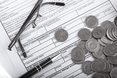 Business documents, eyeglasses, one zloty polish coins and pen  Money and savings concept