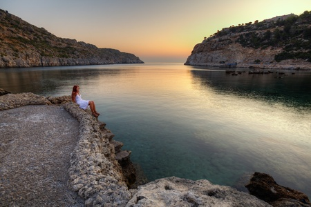Beautiful young woman watching sunrise on Anthony Quinn Bay  HDR photography of greek landscape - Rhodes
