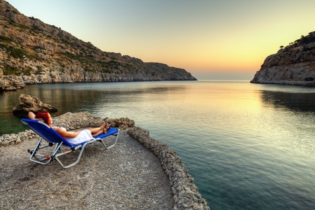 Beautiful young woman watching sunrise on Anthony Quinn Bay  HDR photography of greek landscape - Rhodes Stock Photo - 12733834