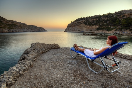 Beautiful young woman watching sunrise on Anthony Quinn Bay. HDR photography of greek landscape - Rhodes. Stock Photo - 12733844