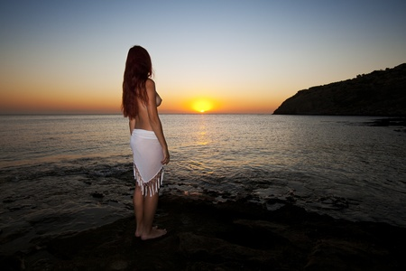 Beautiful young naked woman watching sunrise on Rhodes beach. Greek morning.