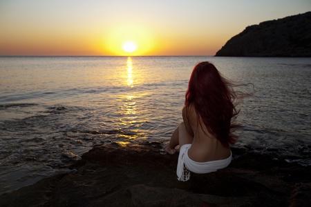 Beautiful young naked woman watching sunrise on Rhodes beach. Greek morning.