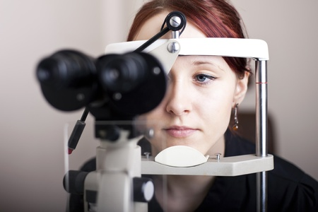 Beautiful young woman having eye test  At the optometrist concept  photo