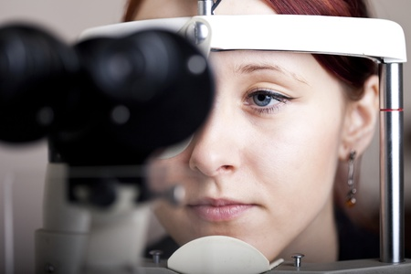 portait: Beautiful young woman having eye test  At the optometrist concept  Stock Photo