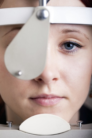 Beautiful young woman having eye test  At the optometrist concept  Stock Photo - 13088381
