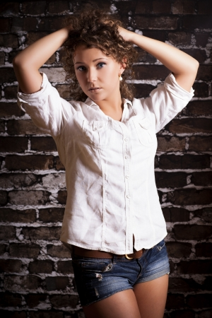 Beautiful young curly hair woman wearing white shirt on brick wall background  Fashion portrait