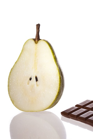 Juicy pear half and chocolate bar. Dessert ingredients. Stock Photo