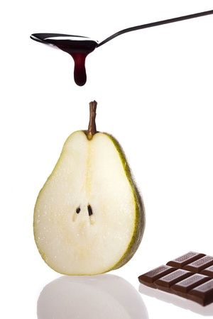 Juicy pear half, chocolate bar and spoon. Dessert ingredients.
