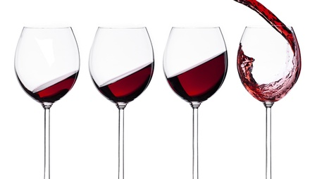 Set of wineglasses with red wine isolated on white background. Splashing drink concept.