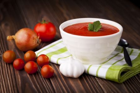Fresh red tomato cream soup in white bowl. Dish and ingredients photography taken on old wooden table. Stock Photo