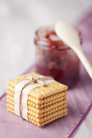 Stack of fresh baked biscuits tied with vintage string and jar of red fruit jam. Sweets composition taken on white table.