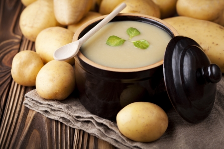Traditional homemade potatoes cream soup served in vintage ceramic bowl. Dish and fresh ingredients composition.