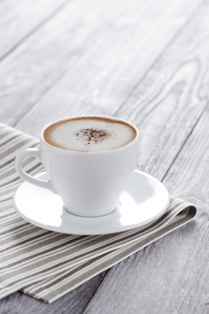 Black coffee served in cup. Espresso doppio decorated with pinch of cacao. Stock Photo