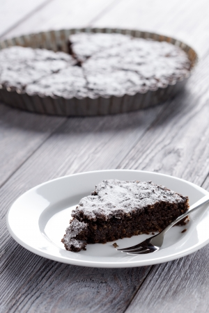 Sweet slice of brownie and whole cake in background. Homemade dessert decorated with sugar powder. Stock Photo