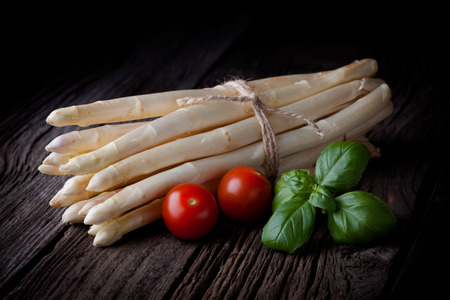Fresh white asparagus bunch, tomatoes and basil composition  Spring vegetables tied with a string taken on white background