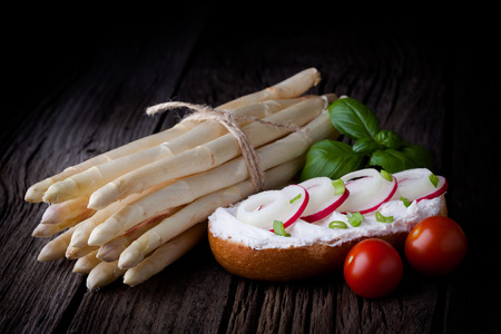 Delicious fresh baked roll  Bun sandwich served with creamy cottage cheese, spring onion, red radish slices, white asparagus and tomatoes, taken on old wooden table  photo