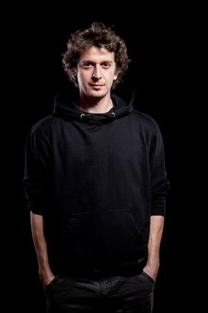 brown hair: Young curly hair caucasian man wearing black hooded sweatshirt. Low key portrait taken on black background.
