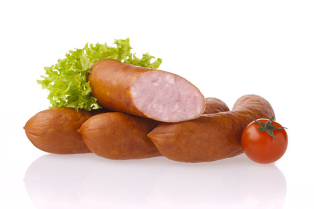 Fresh polish sausages, tomatoes and lettuce. Meat and vegetable composition taken on white background with reflection.