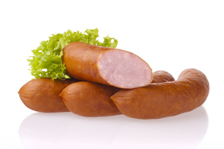 Fresh polish sausages and lettuce. Meat composition taken on white background with reflection.