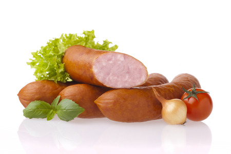 Fresh polish sausages, onion, tomatoes and lettuce. Meat and vegetable composition taken on white background with reflection.