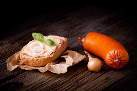 Fresh polish sandwich with meat spread. Pate composition taken on rustic wooden table.