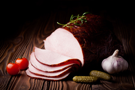 Fresh polish smoked ham slices. Meat composition taken on rustic wooden table.