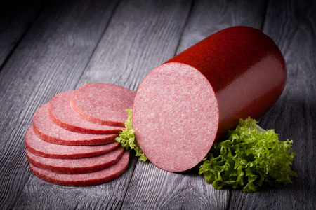 Fresh polish salami sausage slices. Meat composition taken on rustic wooden table.
