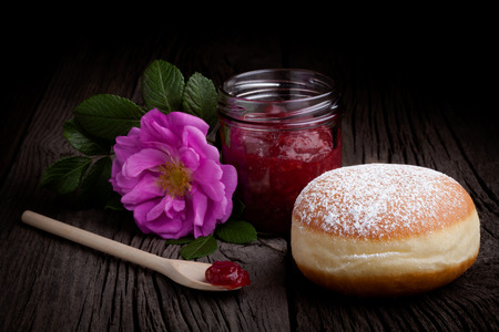 Fresh homemade donut covered by sugar powder frosting, wild rose flower and jar of red fruit jam. Sweets composition taken on rustic table. Stock Photo