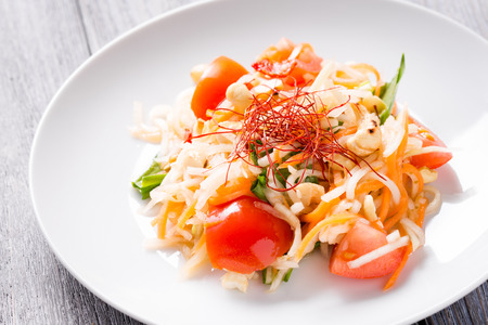 Fresh thai juicy Som Tam salad prepared with kohlrabi, carrot, wild garlic, tomato, cashew nuts and chili stripes. Traditional thai cuisine served on white plate.