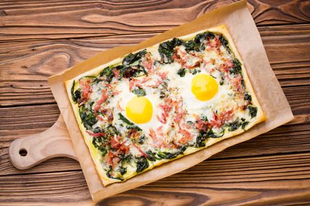 european cuisine: Fresh baked puff pastry egg, spinach, cheese, bacon tart served on wooden table. Traditional homemade european cuisine.