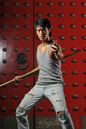 traditional weapon: Young Asian Man Training Martial Arts Stock Photo