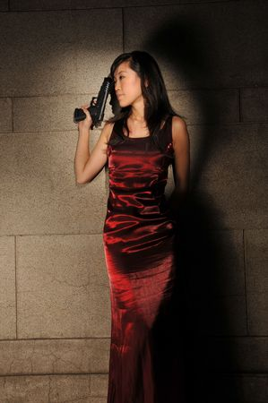 Asian Woman In Red Dress Holding A Gun Archivio Fotografico