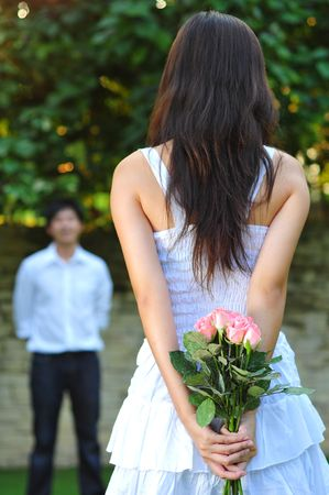 Woman Holding Roses At The Back With Man Standing In The Background Stock Photo