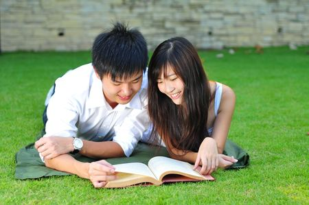 Loving Couple Reading Book In The Park