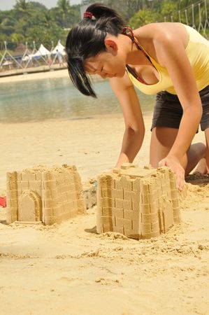 children sandcastle: Young Asian Girl Building Sandcastle By The Beach