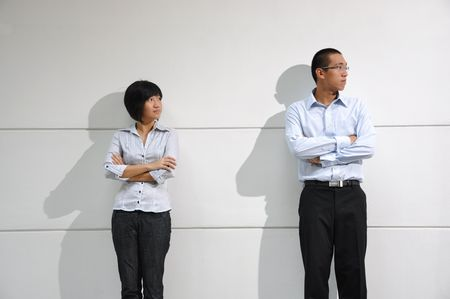 Smart Asian Man & Woman Waiting By The Wall Stock Photo