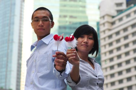 Smart Asian Couple Holding A Hear Shape Stick photo