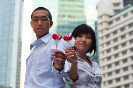 Smart Asian Couple Holding A Hear Shape Stick photo
