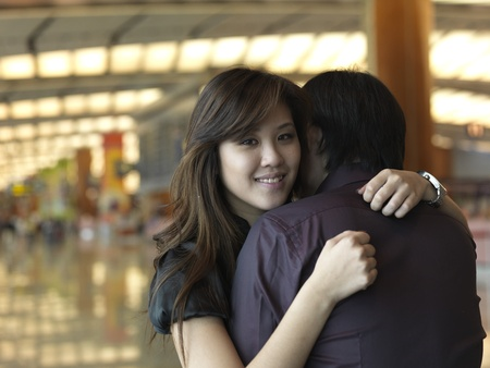 Asian Chinese girl hugging with joy at the airport Foto de archivo