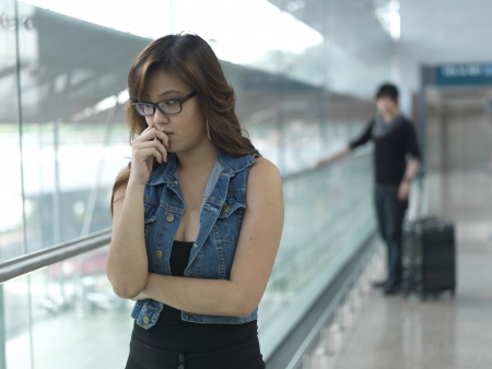 feeling sad: Asian Chinese couple fighting at the airport Stock Photo