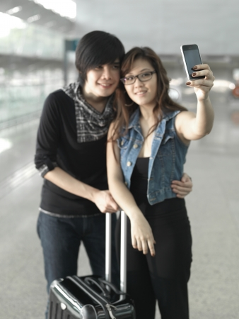 depart: Asian Chinese couple taking self portraits at the airport