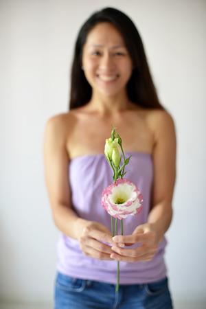 adentro y afuera: Mujer en fuera de foco que sostiene una flor