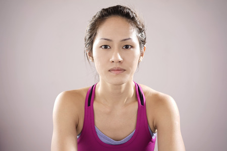 demotivated: Asian chinese female athlete feeling demotivated and staring into deep space.