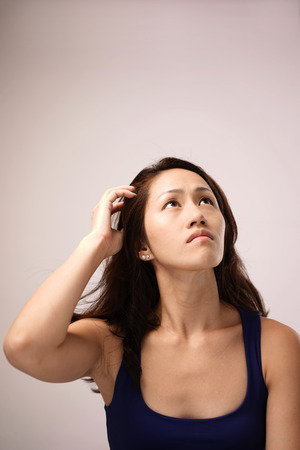 Asian chinese lady feeling puzzled in pink background