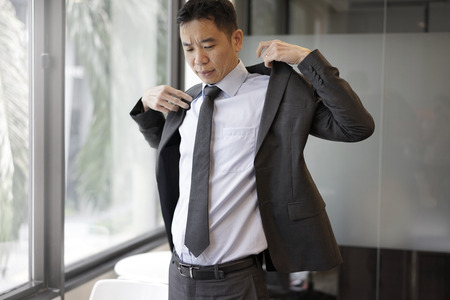 energized: Picture of successful asian man putting on his jacket for corporate meeting